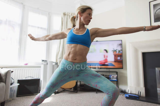 Woman practicing online yoga in living room — Stock Photo