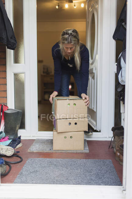 Woman retrieving produce boxes from front stoop — Stock Photo