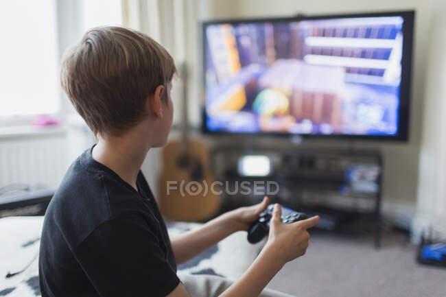 Menino jogando videogame na TV na sala de estar — Fotografia de Stock