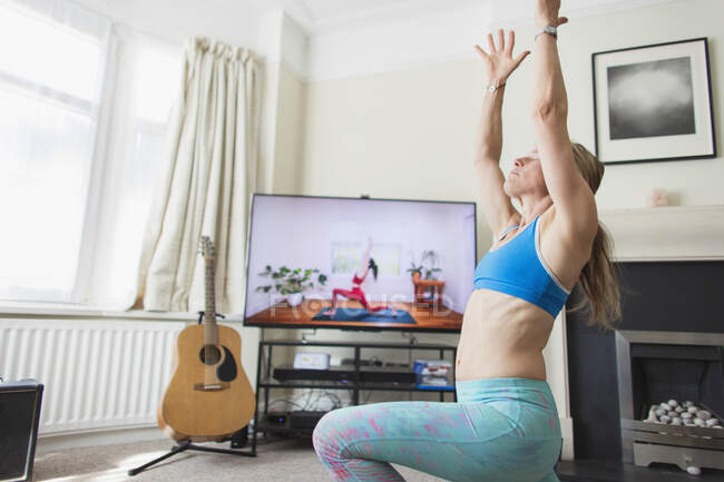 Woman practicing yoga at TV in living room — Stock Photo