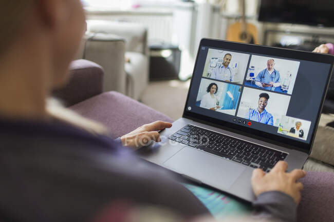 Woman video chatting with doctors at laptop from home — Stock Photo