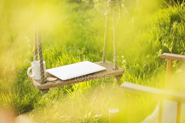 Laptop e tazza di caffè su altalena in giardino soleggiato — Foto stock
