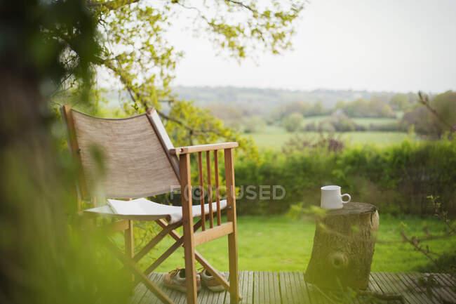 Стул и кофе на спокойном балконе с видом на сельскую местность — стоковое фото