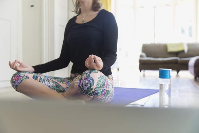 Женщина практикует медиацию на коврике для йоги дома — стоковое фото