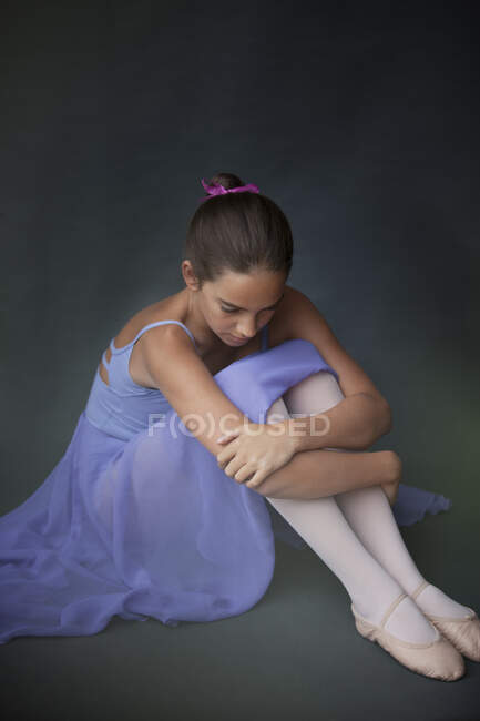 Bailarina abrazando rodillas en estudio - foto de stock