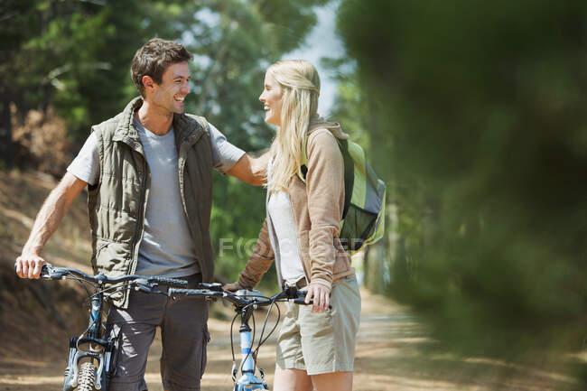 Casal sorridente com bicicletas de montanha na floresta — Fotografia de Stock