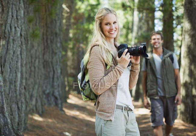 Улыбающаяся женщина с цифровой камерой в лесу — стоковое фото
