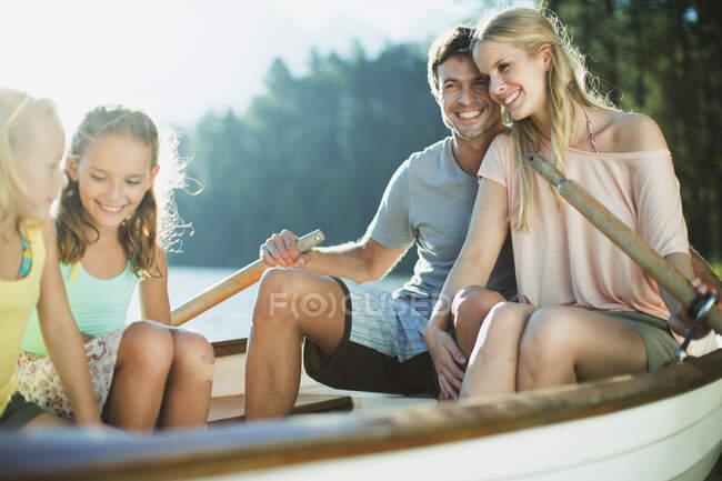 Família sorridente em barco a remos no lago — Fotografia de Stock