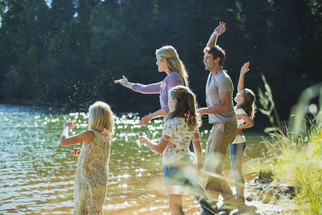 Famiglia che salta pietre sul lungolago — Foto stock
