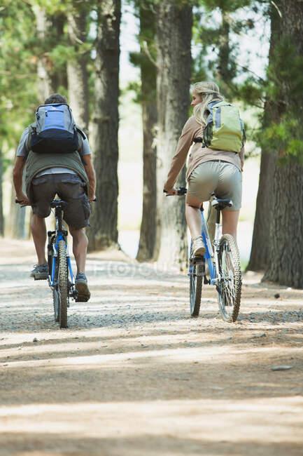 Casal de bicicleta de montanha com mochilas na floresta — Fotografia de Stock