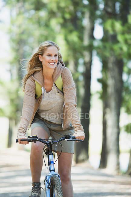 Smiling woman riding mountain bike in woods — Stock Photo