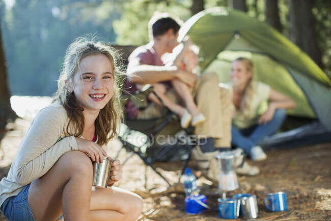 Smiling girl at campsite with family in woods — Fotografia de Stock