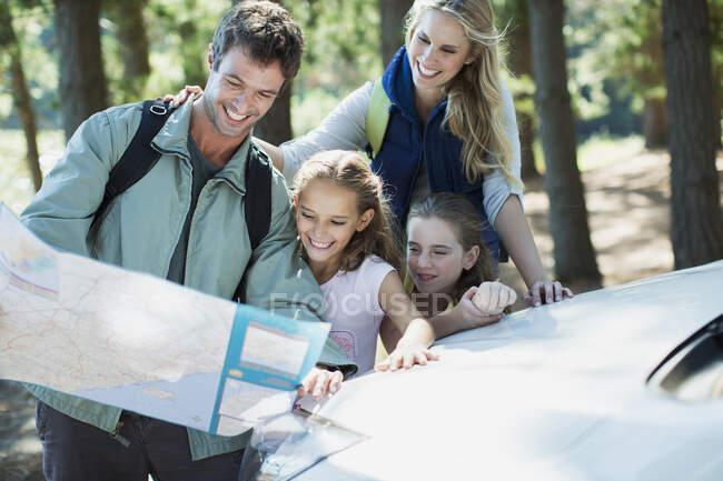 Familie schaut im Wald auf Landkarte — Stockfoto