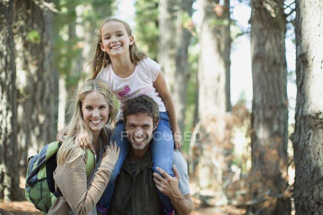 Улыбающаяся семья в лесу — стоковое фото