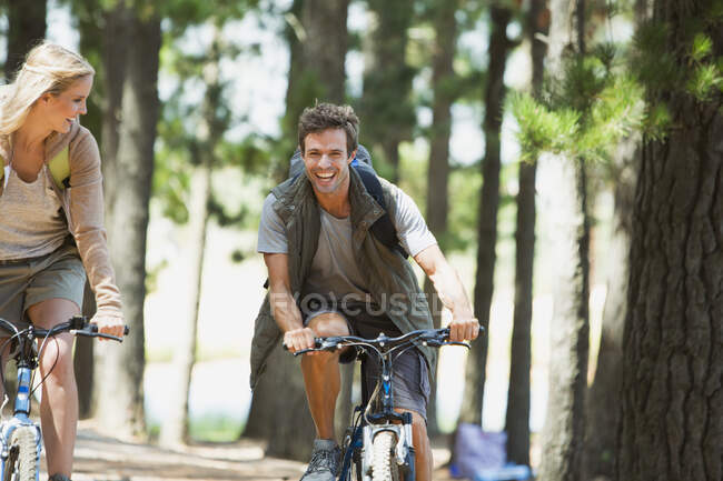 Smiling couple mountain biking in woods — Stock Photo