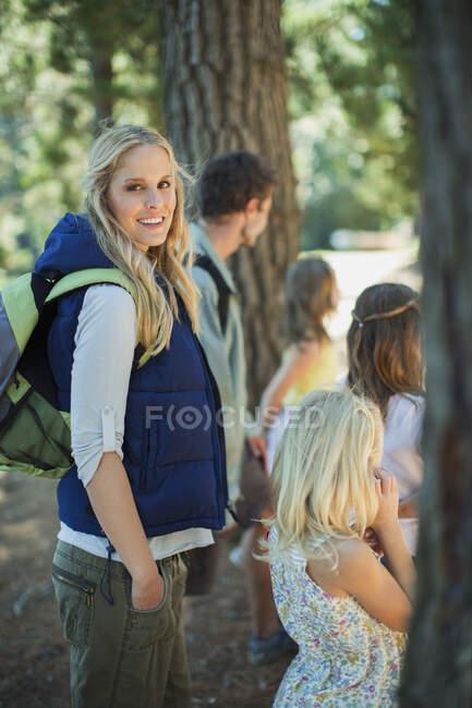 Улыбающаяся женщина в походе с семьей в лесу — стоковое фото