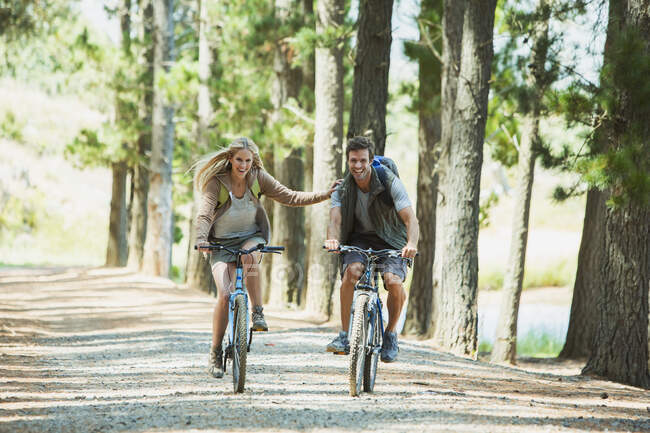 Sorrindo casal mountain bike na floresta — Fotografia de Stock