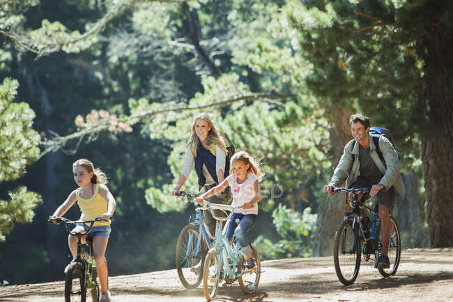 Smiling family bike riding in woods — Stock Photo