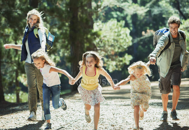 Smiling family holding hands and running in woods — Stock Photo
