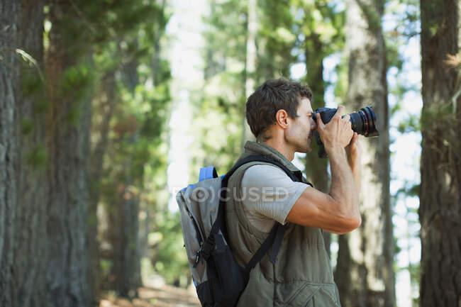 Homem usando câmera digital na floresta — Fotografia de Stock