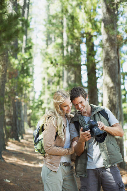 Smiling couple looking at digital camera in woods — Stock Photo