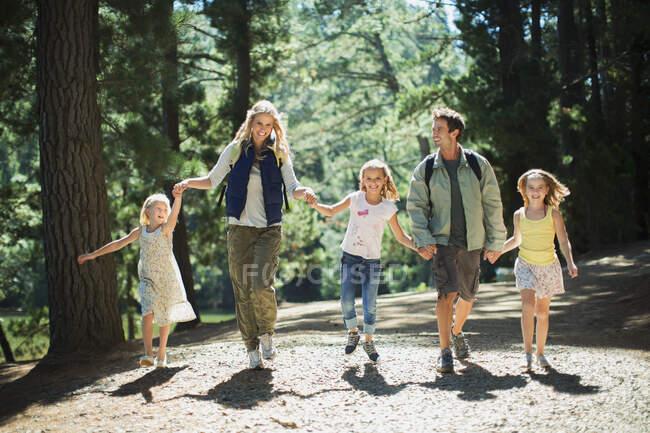 Улыбающиеся семьи держатся за руки и ходят по лесу — стоковое фото