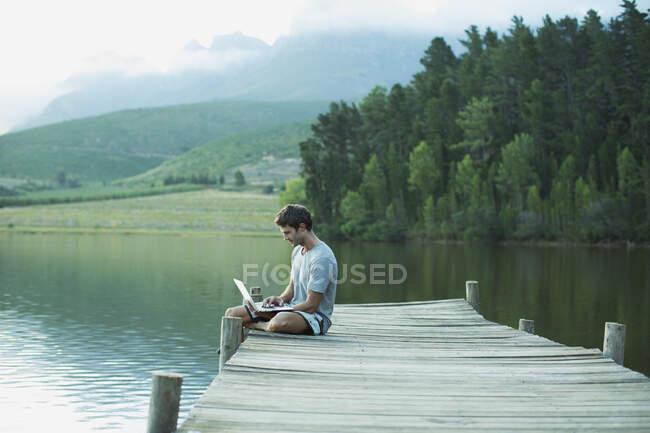 Hombre usando el ordenador portátil en el muelle sobre el lago tranquilo - foto de stock