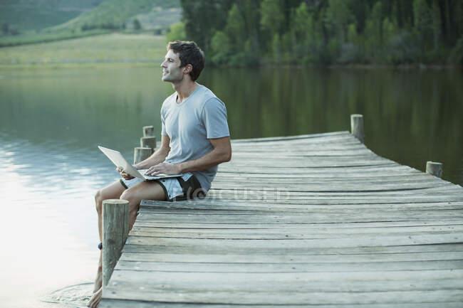 Uomo che utilizza il computer portatile sul molo sul lago — Foto stock