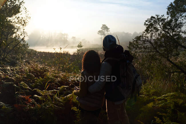 Silhouette young couple hiking and enjoying tranquil nature view — Stock Photo