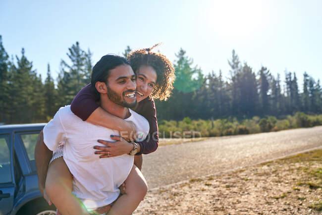 Glückliches Liebespaar huckepack am sonnigen Sommerhimmel — Stockfoto