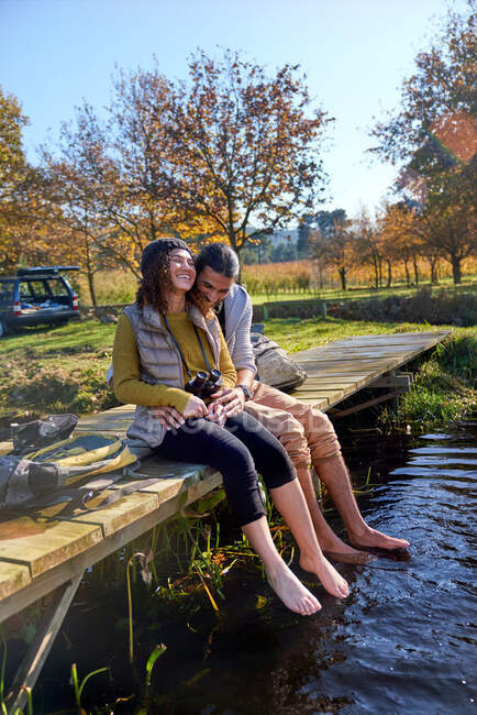 Affectionate barefoot young couple laughing on sunny dock — Stock Photo