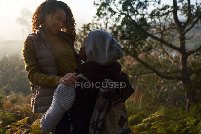 Happy affectionate hiking couple hugging in woods — Stock Photo