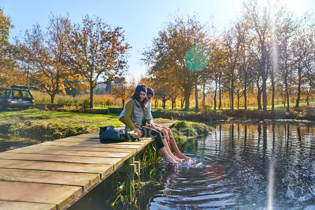 Happy young couple on dock dipping bare feet in sunny autumn lake — Stock Photo