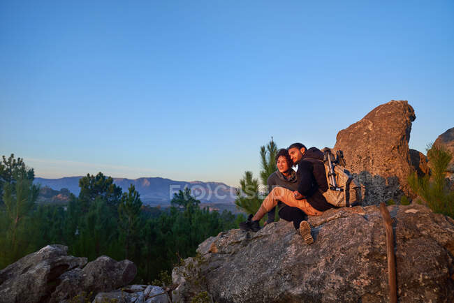 Young hiker couple relaxing on rock and enjoying sunset — Stock Photo