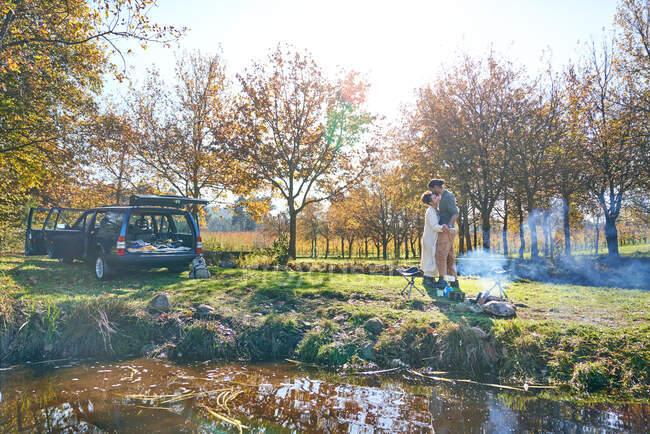 Liebevolles junges Paar zeltet in sonnigem Herbstfeld — Stockfoto