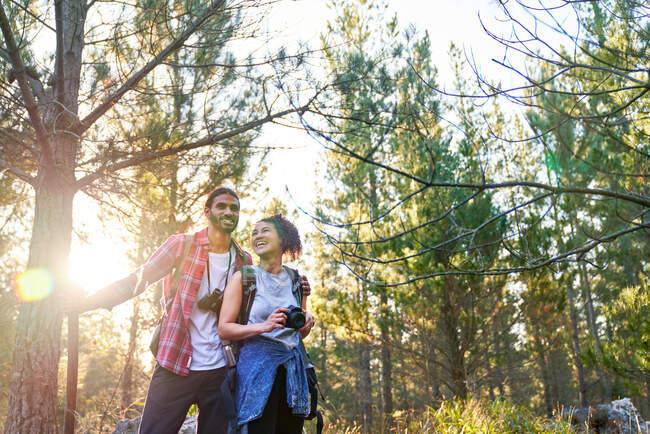 Feliz joven pareja de senderismo con cámara y prismáticos en bosques soleados - foto de stock