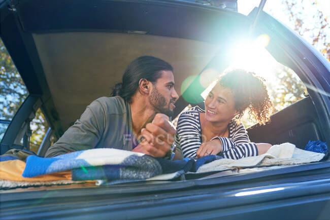 Счастливая молодая пара отдыхает на заднем сиденье солнечной машины — стоковое фото