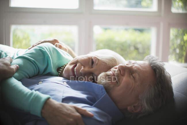 Glückliches Senioren-Paar kuschelt am sonnigen Fenster — Stockfoto