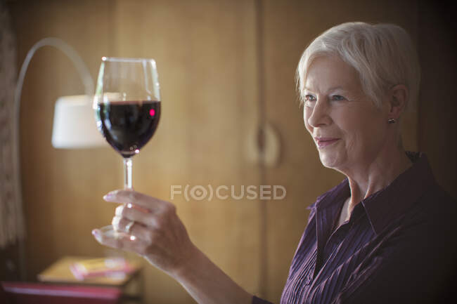 Senior woman enjoying red wine — Stock Photo