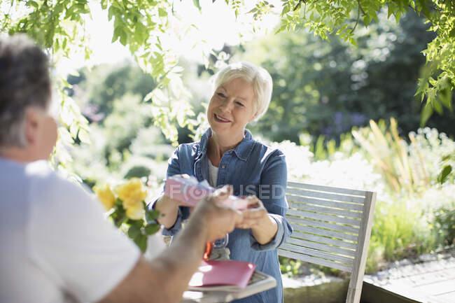 Hombre mayor dando regalo de cumpleaños esposa en patio de verano - foto de stock