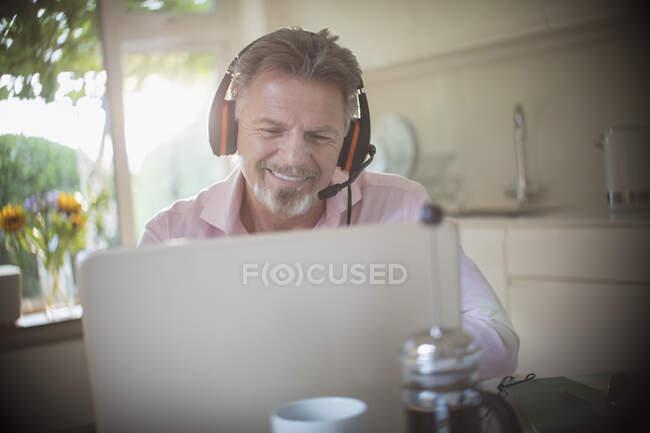 Щасливий старший чоловік з навушниками, що працюють на ноутбуці на ранковій кухні. — стокове фото