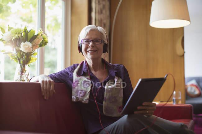 Portrait femme âgée heureuse avec écouteurs et tablette numérique sur canapé — Photo de stock