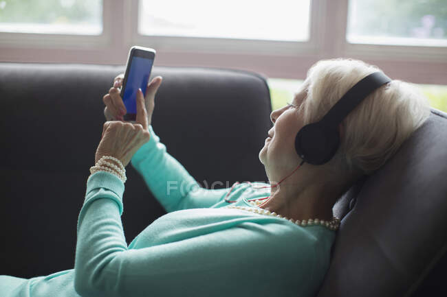 Senior woman relaxing with headphones and smart phone on sofa — Stock Photo