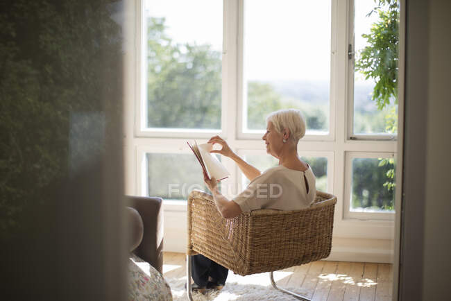 Старшая женщина расслабляющий и чтение книги в гостиной кресло — стоковое фото