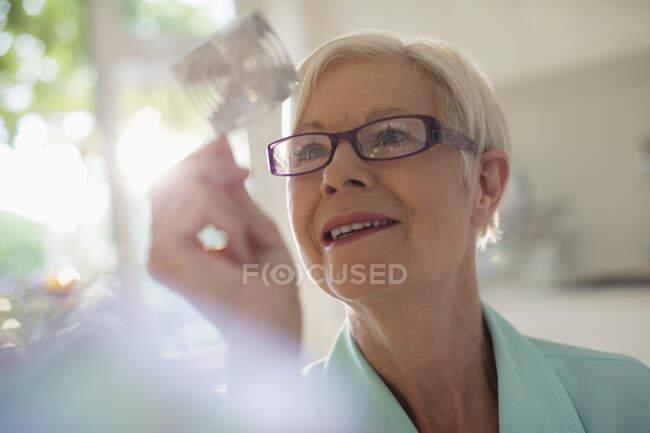 Curiosa donna anziana esaminando cubo alla luce del sole — Foto stock