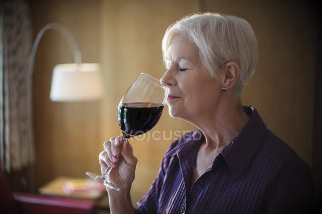 Serene senior woman smelling and tasting red wine — Stock Photo