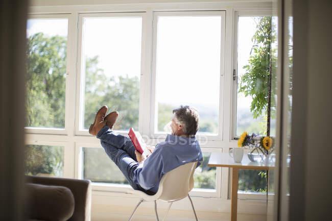 Обережний старший чоловік, який читає книжку з ногами на сонечку. — стокове фото
