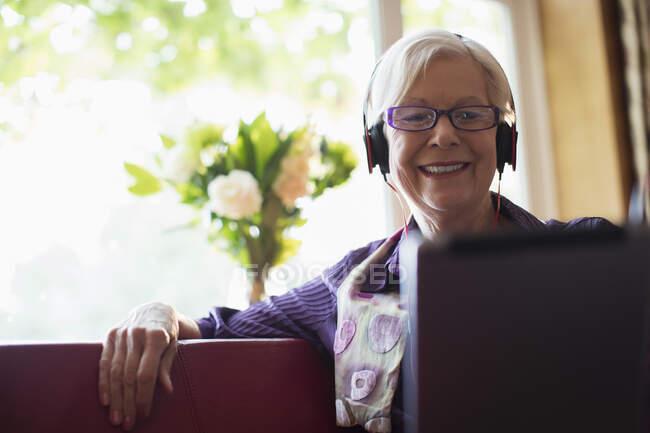Улыбающаяся пожилая женщина в наушниках с цифровым планшетом на диване — стоковое фото
