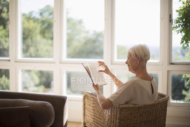 Пожилая женщина расслабляется и читает книгу в солнечной гостиной — стоковое фото