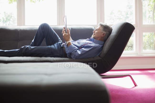 Старший мужчина расслабляется с цифровым планшетом на диване в гостиной — стоковое фото